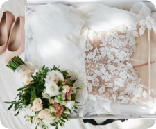 Bridal pink bouquet, white shoes and wedding dress in the background